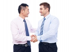 asian and caucasian businessmen shaking hands looking at each other, isolated on white background.
