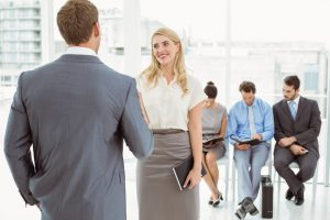 Businesspeople in front of people waiting for job interview in office